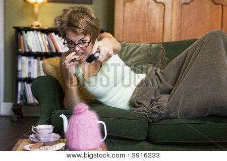 Woman With Remote Control In Hand Eating Chocolate Biscuit