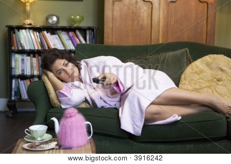 Woman Looking Sad On Sofa With Remote Control In Hand