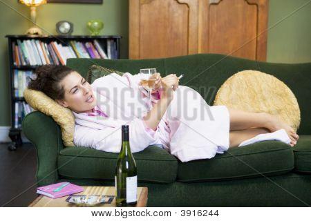 Woman Laid On Sofa Smoking And Drinking