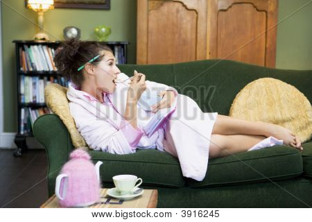 Woman Laid On Sofa Eating