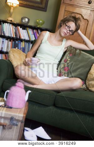Woman Looking Fed Up On Sofa With Tea In Hand