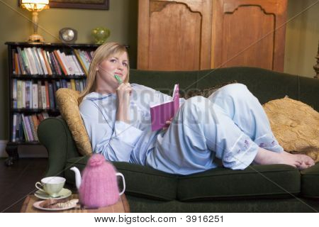 Woman Laid On Sofa With Notebook