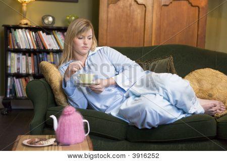 Woman Laid On Sofa Drinking Tea