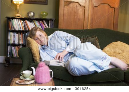 Woman Laid On Sofa Waiting For Phone To Ring