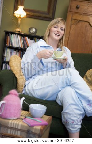 Woman Sat On Sofa Eating