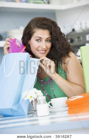 Woman Looking At Shopping Purchases In Tea Room