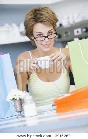Woman Drinking Tea With Shopping Bags On Table