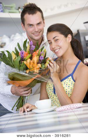 Pareja con ramo de flores en el salón de té