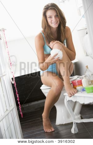 Woman With Exfoliator In Bathroom
