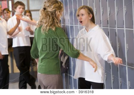 Teen Girl Being Told Off By Teacher In School Corridor