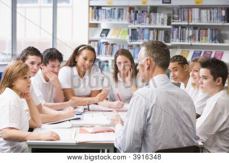 Teacher And Teen Pupils Learning In School Library