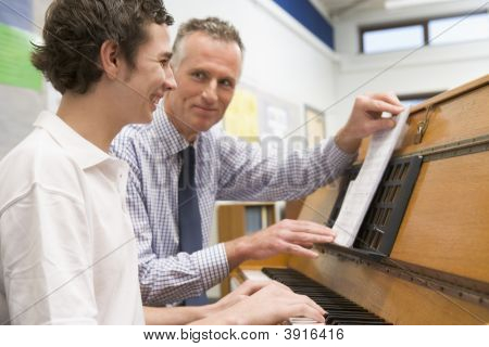 Teacher Helping Teen Pupil To Learn The Piano