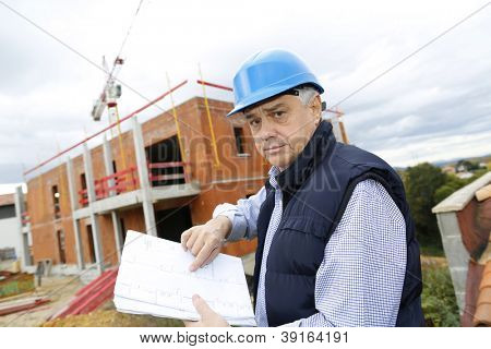 Construction manager checking building project on site