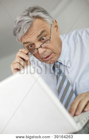 Portrait of businessman with suprised look in front of laptop