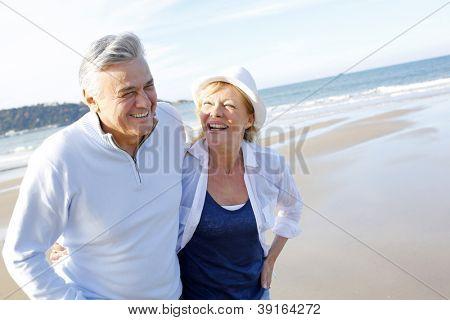 Senior couple walking on the beach in fall season