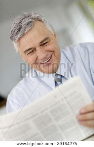 Smiling businessman reading newspaper in office