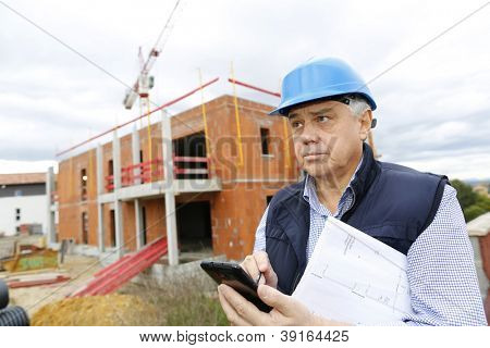Construction manager on building site using smartphone