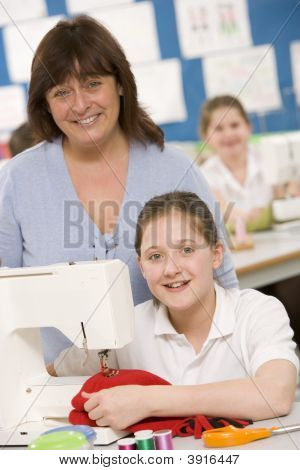 Teacher Helping Pupils In Textiles Lesson