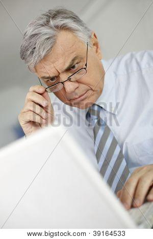 Portrait of businessman with perplexed look in front of laptop