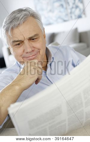 Senior man reading news with perplexed look