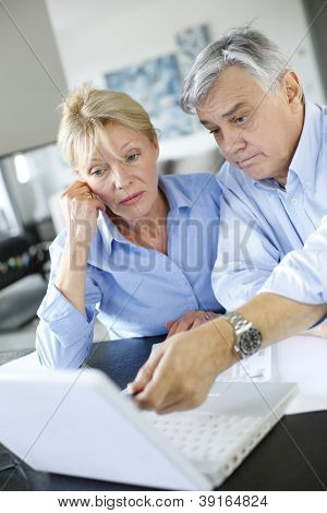 Senior couple inquiring bank website for help