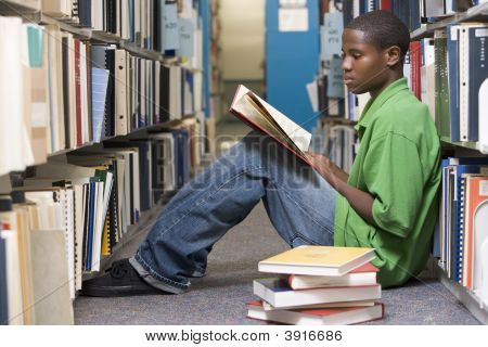 Man Sitting On Floor In Library Reading Book