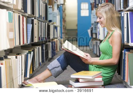 Woman Sitting On Floor In Library Reading Book
