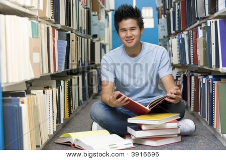 man sitzen auf Boden in Bibliothek, Buch hält