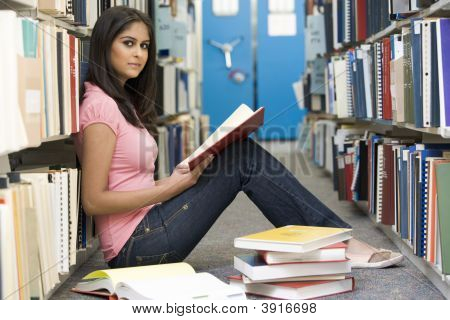 Woman Sitting On Floor In Library Holding Book