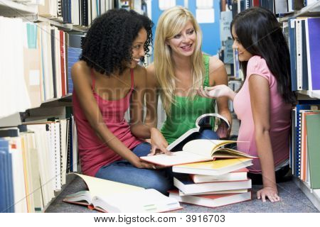 Three Women Sitting On Floor In Library With Books