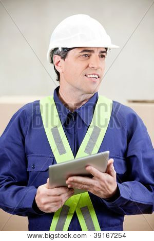 Warehouse worker with digital tablet standing in warehouse