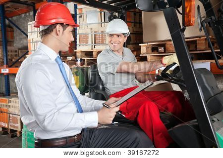 Happy forklift driver communicating with male supervisor at warehouse