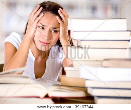 Tired female student at the library looking very frustrated