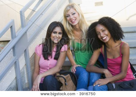 Three Women Sitting On Staircase Outdoors Smiling (High Key)