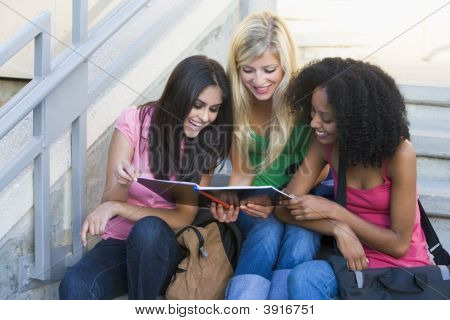 Three Women Sitting On Staircase Outdoors Looking At Notebook (High Key)