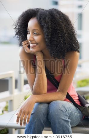 Woman Sitting On Bench Outdoors Smiling (Selective Focus)