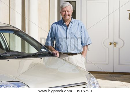 Senior Man Standing With His Car Outside His Home