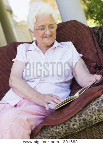 Senior Woman im Freien sitzen auf einem Stuhl ein Buch zu lesen