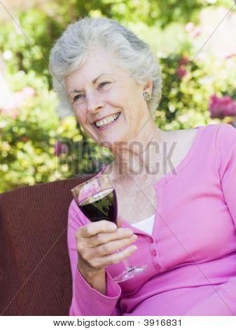 Senior mujer sentada al aire libre en una silla con una copa de vino tinto