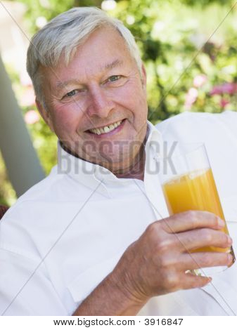 Senior Man Sitting Outdoors With A Glass Of Orange Juice