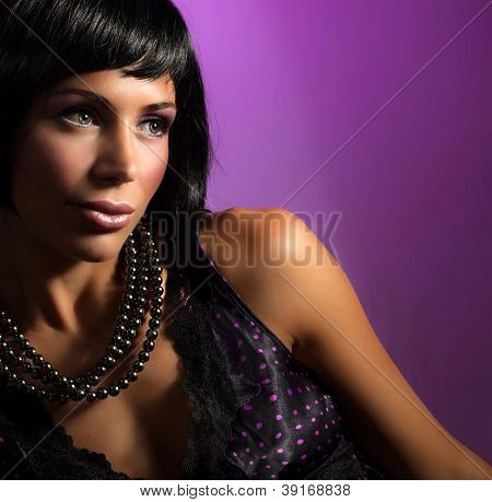 Image of gorgeous woman wearing glamorous necklace, closeup portrait of cute female in luxury jewelry isolated on purple background, young lady with stylish makeup and hairstyle, beauty concept