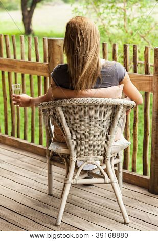 Photo of beautiful girl sitting on veranda and enjoying calm weather, rear view of blond female sit in chair on the balcony, drinking healthy mineral water and watching for peaceful nature