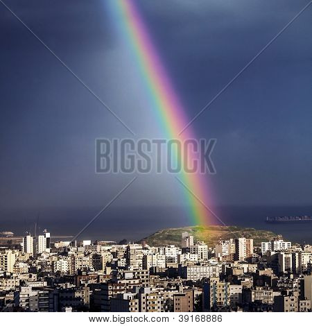 Photo of bright colorful rainbow over city, sun shining in rainy day, beautiful colors phenomenon in dark blue sky, overcast weather, nature landscape in the town, rain season