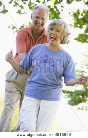 Senior Couple Walking In Park Together