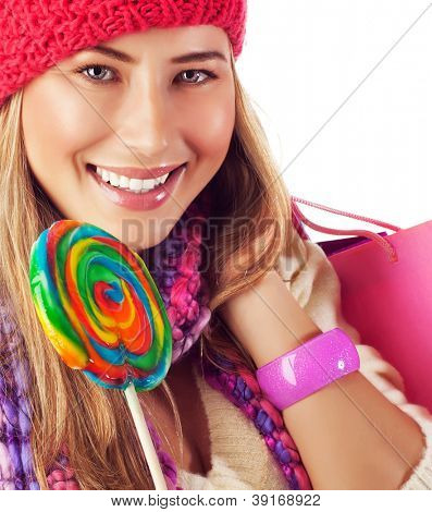 Photo of young beautiful woman lick big colorful lollipop and holding pink shopping bag in hand, closeup portrait of happy woman with beautiful smile wearing red winter hat, Christmas eve concept