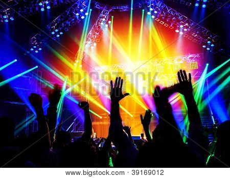 Rock concert, happy people silhouettes, raise up hands, disco party with large group of dancing man, bright colorful stage lights, active lifestyle, music entertainment, nightclub, new year eve