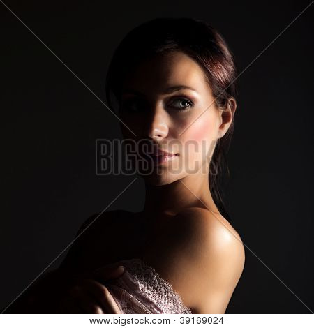Picture of sexy young lady isolated on black background, stylish woman with dark hair wearing seductive lace dress, pretty female in pink openwork with naked shoulder, sensuality and beauty concept