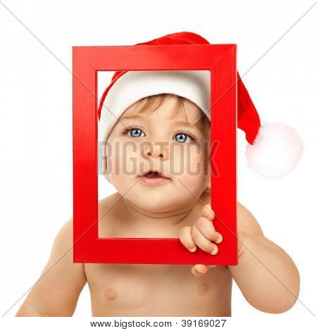 Photo of cute baby boy wearing Santa Claus hat, closeup portrait of curious infant looking through red Christmas frame isolated on white background, happy childhood, winter holidays, New Year eve