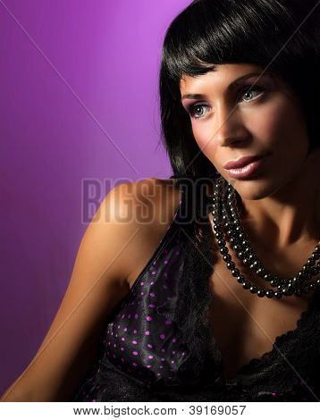 Photo of beautiful woman with black pearl isolated on purple background, attractive brunet female wearing stylish beads, Christmas eve, fashionable model, beauty concept