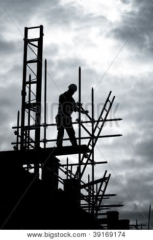silhouette of construction worker on scaffold
